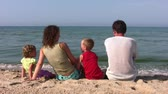 parent : Family of four sitting on beach, behind