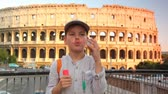 play : boy blow soap bubbles on pedestrian crossing on background of Colosseum in Rome Stock Footage