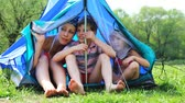 grass : Young woman with little son and daughter sit talking in tent at forest on summer day Stock Footage