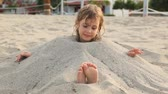 travessura : little girl with wet hair smiles siting filled up with sand on neck on beach