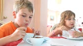 summer : Boy and girl with curly hair eat granola and yogurt for breakfast Stock Footage