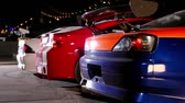 taillight : Exhaust smoke goes from tubes of few cars with colorful sport design at night