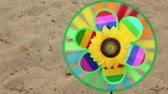 levou : Round multi-colored toy with a sunflower in the center is set in the ground and rotates, then the girl took it