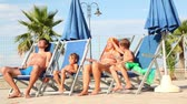 взял : Parents and two kids are sitting in deckchairs, and stoped playing hands, begin taning Стоковые видеозаписи