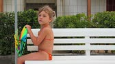 bagatela : Little girl in swimsuit are sitting on bench with colored toy in hands, and telling something