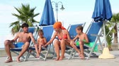 magyarázza : Parents and two kids are sitting in deckchairs, and playing hands Stock mozgókép