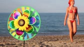 bagatela : Multicolored toy with sunflower in center, that spins on the background of sea and a woman walking on shore Vídeos