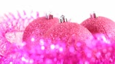 lentejoula : Three glitter christmas tree balls rotate, surrounded by purple tinsel, isolated on white.