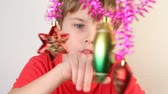 lentejoula : Serious boy play with christmas-tree decoration, which hang on purple tinsel. Vídeos