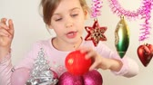 lentejoula : Little girl play with different varicoloured christmas-tree decoration