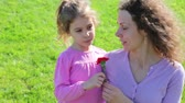goździk : Mother and her little daughter talk about WWII at background of green grass