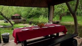 mere : Table is set in summerhouses ashore of small pond at among trees at summer, shown in motion