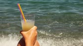 fundus : Hand rests on knee and holding glass with cocktail with tubules, sea surface behind Stock Footage