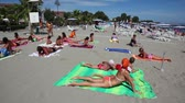 pessoal : CALABRIA, ITALY - JULY 30: Group of people lay on beach and study yoga, at summer sunny day on July 30, 2010 in Calabria, Italy. Italians are very respect family, whether close relative or distant Stock Footage