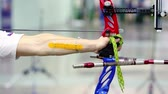 feathering : Man engage in archery, focus on bow sideview closeup