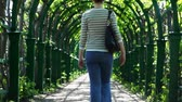 pacing : young woman leaves through arched corridor braided green plants by spring day Stock Footage