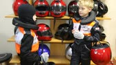 karting : Two boys choose to helmets for on go-cart racings, indoor Stock Footage