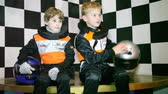 karting : Boys sit in uniform for go-cart racing and wait the beginning of races