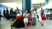 pessoal : Mother and her two kids boy and girl sit in airport and reading book, their luggage stand near