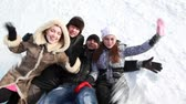 funtime : Group of young people are lying on the snow and laughing.