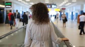 pacing : Curly-headed woman in grey moving on speedwalk at airport, back view Stock Footage