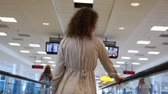 pacing : Curly-headed woman in grey moving on speedwalk and looks around at airport, back view Stock Footage