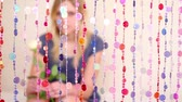 clothe : Girl sit behind beads curtain, watch and hold white flower, blurred Stock Footage