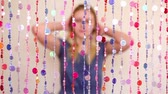 clothe : Young girl sit and corrects hair behind curtain of plastic beads, not in focus