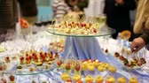 clothe : Hands take canapes from appetizer table with wine and other delights, people stand around
