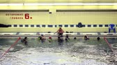 clothe : MOSCOW - DECEMBER 5: Coach teach divers group wich float near edge at swimming pool of Russian State University of Physical Education, Sport and Tourism, on December 5, 2010 in Moscow. Program of competitions in diving involves combined swimming 300 meter
