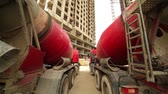 cabine : Two concrete mixer stand near unfinished tall high-rise buildings