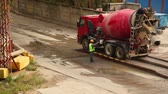 cabine : Two workers wash concrete mixer, one cleans wheels, second scour concrete tube