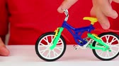 miniatura : Boy play with toy bike, rotates handlebars, try to make trick but fall Stock Footage