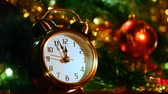 remaining : alarm clock at three minutes remaining before New Years in front of festive lights Christmas tree, close-up