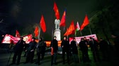 manifestação : MOSCOW - MARCH 17: Several communists stand with flag in front of monument at approved meeting near metro station Chistiye Prudy on March 17, 2011 in Moscow, Russia.
