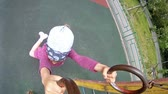 little : Little girl hang on sports rings at playground in house yard Stock Footage