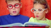 brother : Two kids boy and little girl sit together and read book in glasses