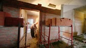 fixer : Two workers build partition between rooms at construction site, panoramic motion