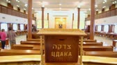 judaísmo : Several people walk in synagogue with jewish wooden box for charity - CDAKA, closeup view