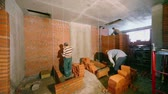 fixer : Few workers build brick walls in room at construction site