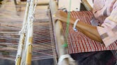 Traditional Thai textile manufacture in craft village, Old women work on wooden weaving thread machines and spin yarn creating cotton fabric. Chaing Mai, Thailand. Stock Footage