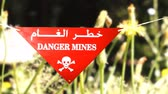warning sign in front of a minefield