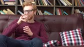 rood haar : Red-haired man sitting in library drinking hot tea relaxed