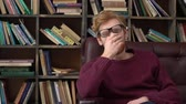 rood haar : Red-haired man sitting in library massaging nasal bridge
