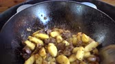 kitchenware : frying of potatoes with meat, onions and tomatoes in a cooking pot on a gas grill
