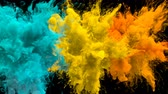 Cyan, Yellow, Orange Color Burst - Multiple colorful smoke powder explosion fluid ink particles slow motion alpha matte isolated on black Stock Footage