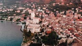 lombardia : Lake Lago Garda - view of Malcesine village. Old castle on rock Italy. Aerial video sunset.