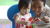 female : Little asian girl and mother playing with colorful construction blocks on table