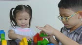 Little asian children playing with colorful construction blocks on table Wideo