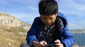 Young asian boy playing games on smart phone outdoor Wideo